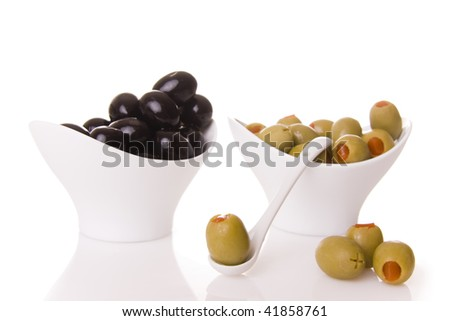 Black and green olives isolated on white - Focus on the olive on ten spoon