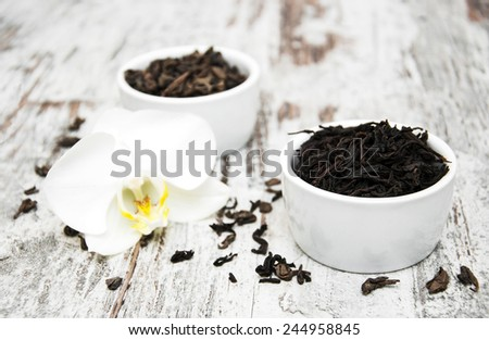 Black  and green tea with orchid flower on a wooden  background - stock photo