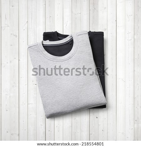 Black and grey jumpers on white wood background - stock photo