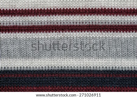 Black and grey knitting wool with red and white stripes texture background. - stock photo