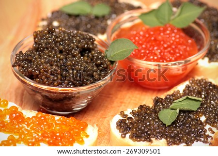 Black and red caviar in a glass container. Sandwiches with caviar.  - stock photo
