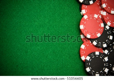 Black and red gambling chips on green felt background with copy space - stock photo