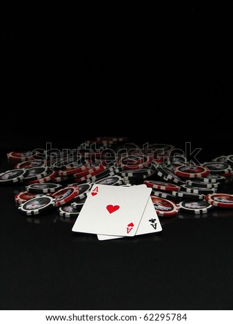 Black and red poker chips and cards isolated on black background - stock photo