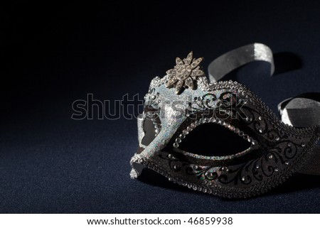 black and silver mask on a black background - stock photo