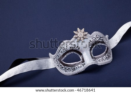 black and silver mask  on dark  background