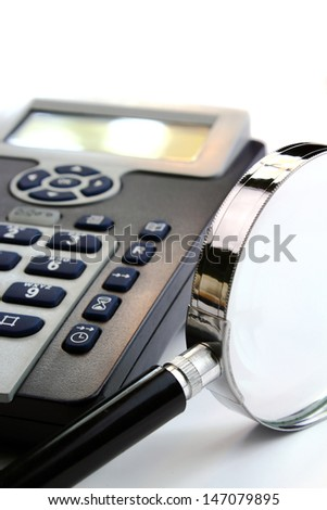 Black and silver telephone and magnification glass