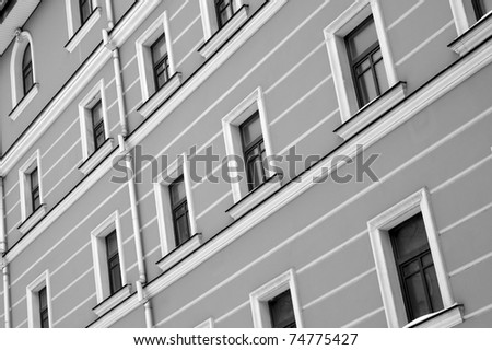 Black and the white image of windows on a wall of an old building - stock photo