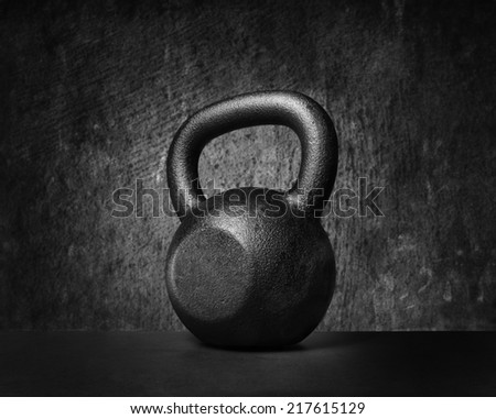 Black and whit image of a rough and tough heavy 30 kg 66 lbs cast iron kettlebell. - stock photo