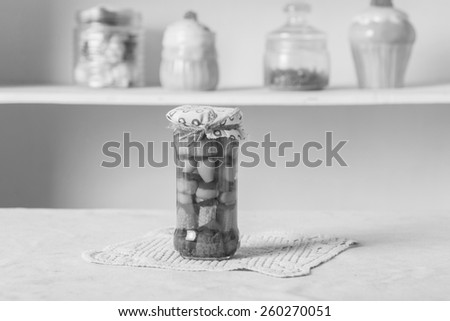 black and white, a small glass jar with conservation, corn, peppers, mushrooms - stock photo
