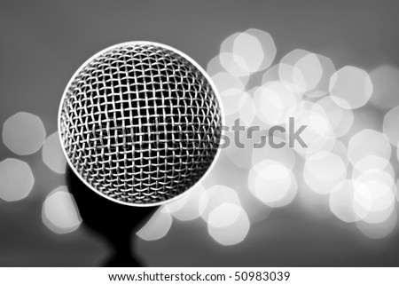 Black and white abstract image of microphone with lights in background. Macro with extremely shallow dof. - stock photo