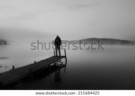 black and white abstract landscape with man stand on wooden bridge in sunrise lake  - stock photo