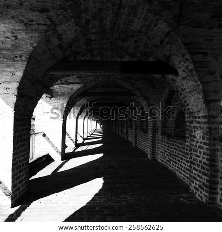 Black and white abstraction brick corridor.Special toned photo in vintage style - stock photo