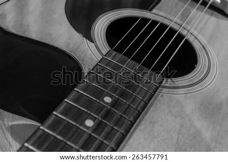 Black and white acoustic guitar with sound hole and pick guard