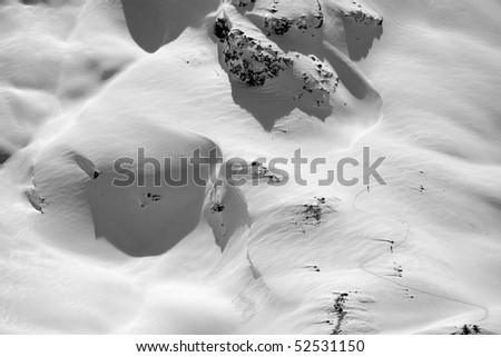 Black-and-white aerial view of skiers climbing up a mountain using skis and climbing skins to reach the summit. Horizontal shot. - stock photo