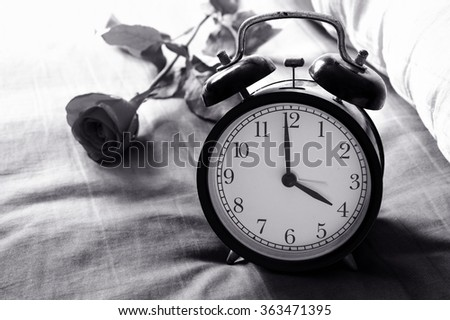Black and white alarm clock on bed at home / Alarm clock