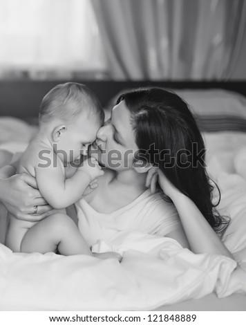 Black and White Art photo of beautiful mother embrace baby boy,  focus on mother - stock photo