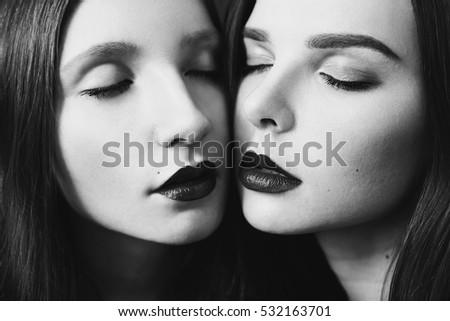 Black and white art photography monochrome, beauty portrait of two red-haired girl on the black and red background. Two lesbian women. Long red hair. Love between girls.