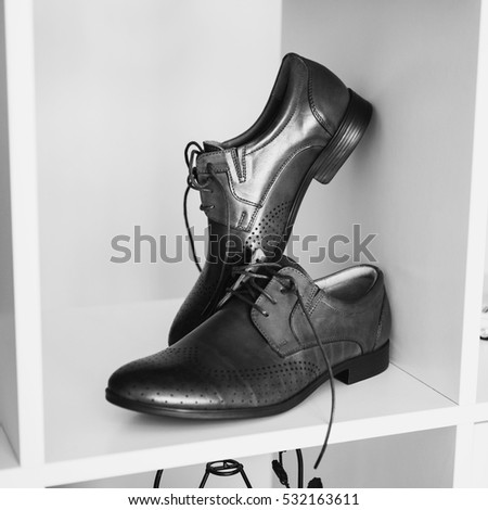 Black and white art photography monochrome, man's shoes stand on a shelf. Men's style, fashion. Charges groom.