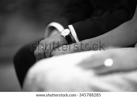 Black and white artistic digital rectangular horizontal photo of the bride wearing white wedding dress and bridegroom holding hands during church wedding marriage ceremony. - stock photo