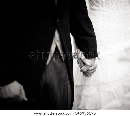 Black and white artistic digital rectangular horizontal photo of the bride wearing white wedding dress holding hands with the bridegroom wearing long jacket dark morning sui - stock photo
