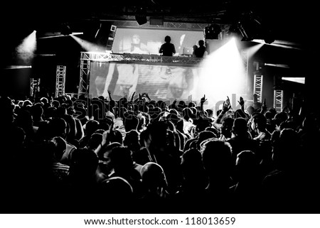 Black and White Audience Crowd Silhouette Dancing to DJ Pete Tong at Cream Nightclub Party. Nightlife Lazer Show Hands In Air With Smoke Cannon Blast - stock photo