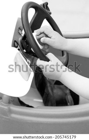 Black and white baby hands holding a wheel