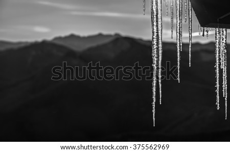 Black and White, Back Lit Icicles Hang with Cascade Mountain Range in Distance - stock photo