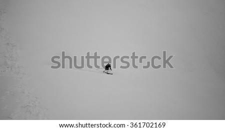 Black and white background of skier riding on slope- bulgarian winter resort - stock photo