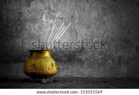 black and white background with a golden bowl with  incense - stock photo
