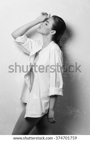 black and white , beautiful woman with brown hair and perfect skin in fashion pose with unbuttoned white shirt and nude legs