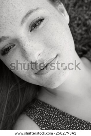 Black and white beauty portrait of an attractive young beautiful tourist woman laying down on grass in a park, relaxing on a summer holiday, smiling. Healthy living and beauty lifestyle, exterior.