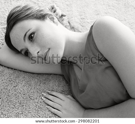 Black and white beauty portrait of young woman laying on a bed blanket at home wearing a dress and gently smiling, looking away thoughtful, home bedroom interior. Beauty feminine indoors lifestyle. - stock photo