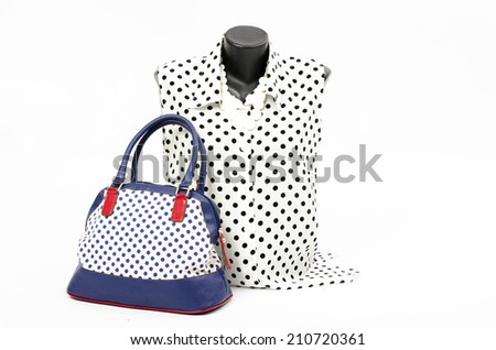 Black and white blouse on mannequin with matching accessories. Elegant blouse on tailor's dummy with matching colorful blue purse and white necklace - stock photo