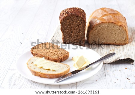 Black and white bread with butter on the table, selective focus - stock photo