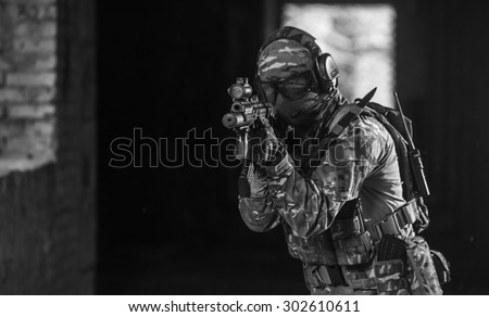 Black and White. BW. Airsoft strikeball player in military soilder uniform in action - stock photo