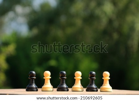 Black and white chess pawns mixed - stock photo