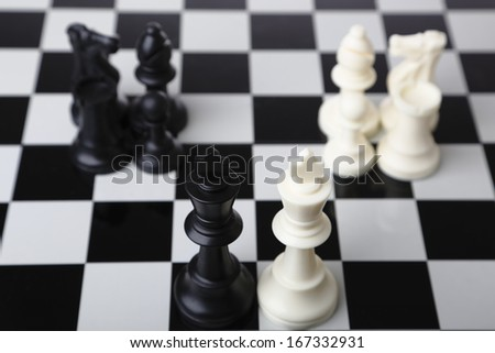 Black and white chess pieces merging together on a chessboard - stock photo