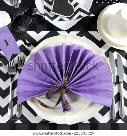 Black and white chevron with purple theme party luncheon table place setting for Melbourne Cup, Australian public holiday, horse race event - overhead view. - stock photo
