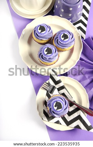 Black and white chevron with purple theme party luncheon table place setting for Melbourne Cup, Australian public holiday, horse race event cupcakes with copy space vertical. - stock photo