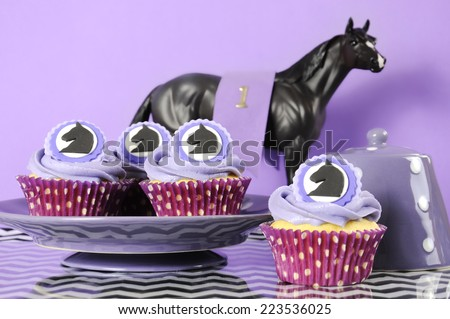 Black and white chevron with purple theme party luncheon table place setting for Melbourne Cup, Australian public holiday, horse race event cupcakes against purple background. - stock photo