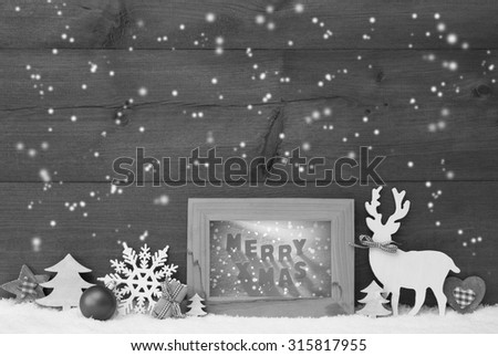 Black And White Christmas Decoration With Reindeer Christmas Trees Snowflakes Ball On Snow. Picture Frame With English Text Merry Xmas. Christmas Card For Seasons Greetings. Wooden Background - stock photo