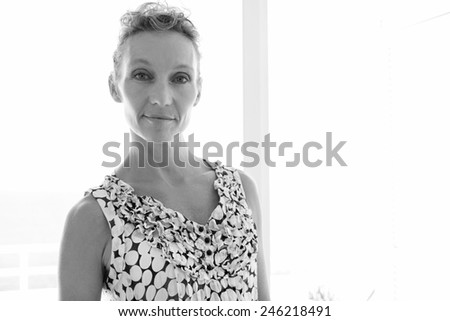 Black and white close up beauty portrait of a healthy mature professional woman smiling at the camera standing against a bright window in a home office space, interior. Business and lifestyle at home. - stock photo