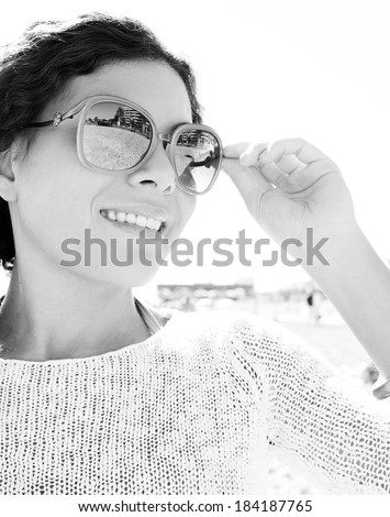 Black and white close up beauty portrait of a smiling young woman standing against a sunny sky during a summer holiday, holding her shades. Beauty and travel lifestyle, outdoors.