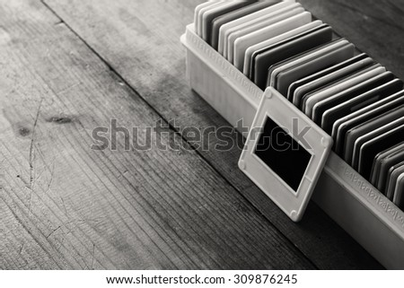 black and white close up image of old slides frames and old camera over wooden table  - stock photo