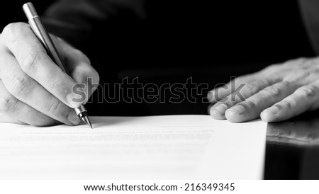 Black and white close up image of the hands of a businessman writing or signing a document with a fountain pen.