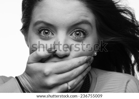 Black and white close-up image of young female holding her right hand over her mouth, landscape format. - stock photo
