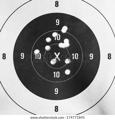 Black and white, Close up of a shooting target and bullseye with bullet holes - stock photo