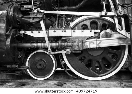 Black-and-white close-up of locomotive wheels and engine