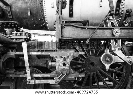 Black-and-white close-up of locomotive wheels and engine - stock photo