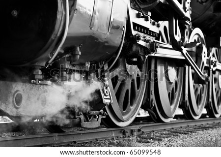 Black and White close-up of wheels on an antique steam train waiting to leave the station - stock photo